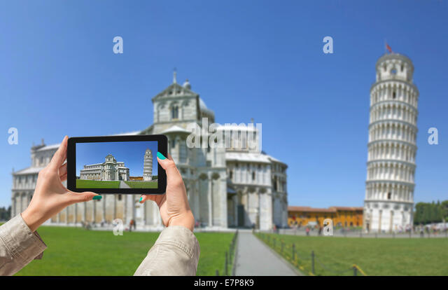 Young girl traveling and taken pictures Leaning Tower in Pisa, with tablet - Stock Image