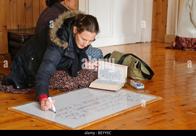Female Hare Krishna devotee transcribes a passage from the Bhagavad Gita onto a whiteboard for discussion - Stock Image