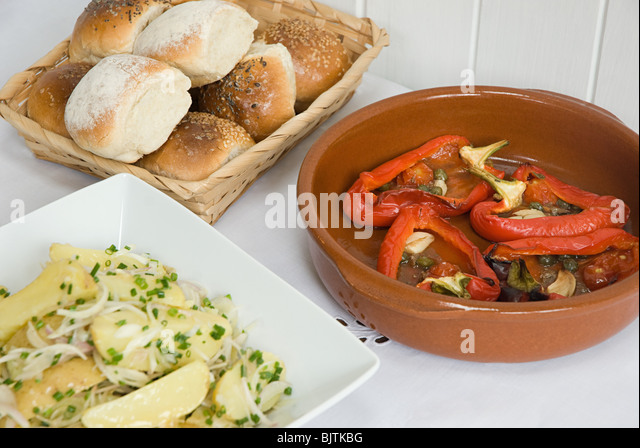 Potato and roast pepper dishes with bread rolls - Stock Image