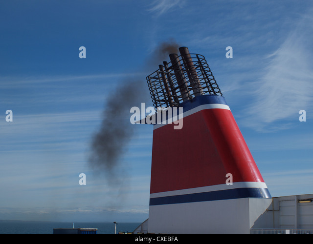 Thick acrid smoke rising through the ships thunnel  as the vessel sails over the Irish sea between England and Ireland. - Stock Image