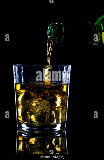 Whiskey being poured into a glass of ice against a black background - Stock Image