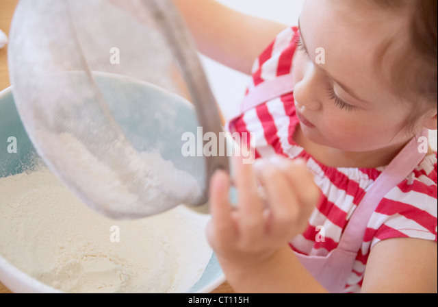 Girl sifting flour in kitchen - Stock Image