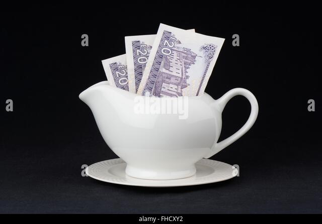 Concept image of 3 twenty pound notes of Royal Bank of Scotland denomination inside a gravy jug - Stock Image
