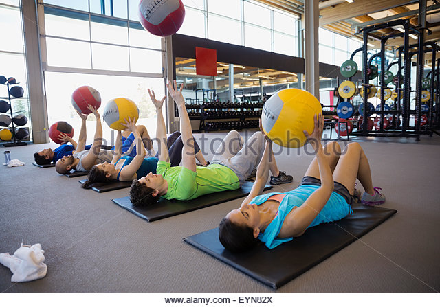 Exercise class throwing medicine balls overhead in gym - Stock Image