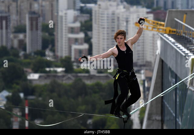 Yekaterinburg, Russia. 9th Aug, 2017. Tightrope artist Maxim Kagin walks on a rope stretched between two skyscrapers - Stock Image