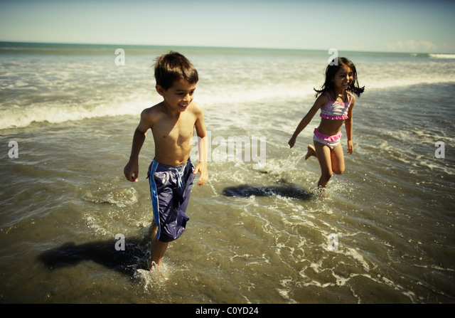 Brother and sister at the seaside, Waitarere beach, New Zealand - Stock Image