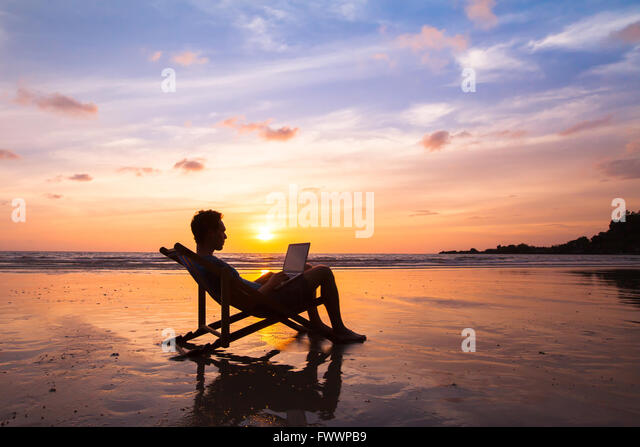 silhouette of happy business man with laptop working on the beach - Stock Image