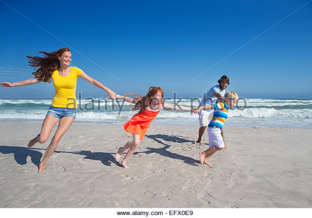 Happy family holding hands, running and pulling each other along sunny beach - Stock-Bilder