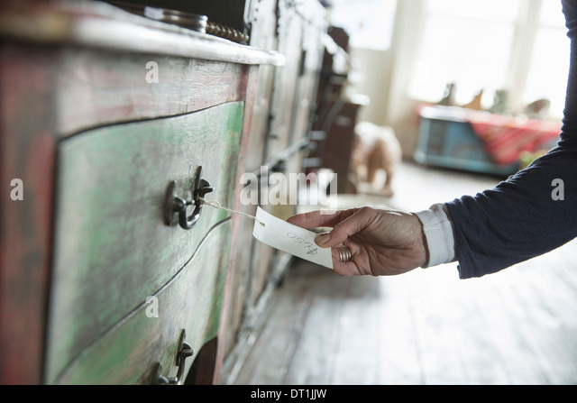 An antique store in a small town with objects and furniture from the past A woman's hand holding the label and - Stock Image