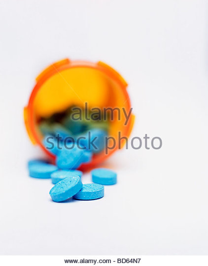 Blue Pills Spilling From Medicine Bottle - Stock Image