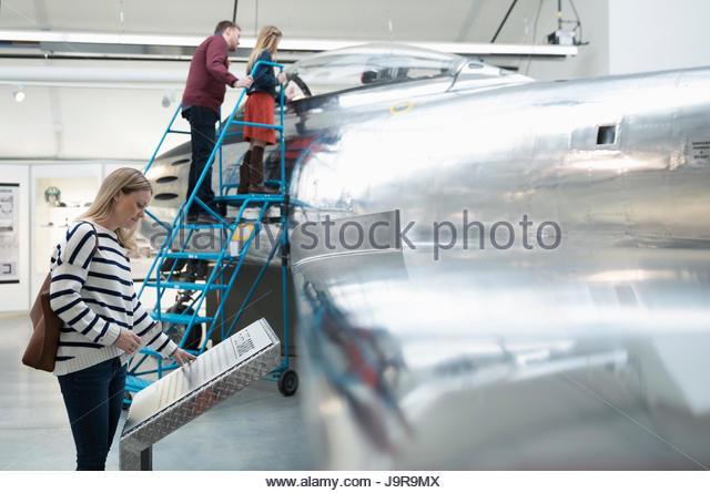 Family looking at airplane in warm museum hangar - Stock-Bilder