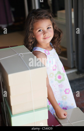Portrait of a cute little girl standing by the stack of objects - Stock Image