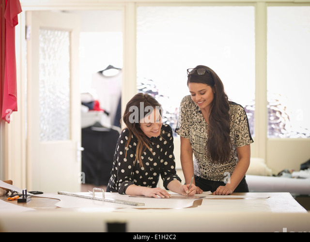 Fashion designers working together in fashion studio - Stock Image