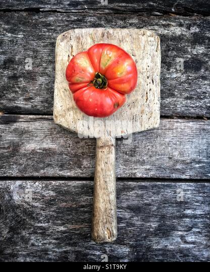 Heirloom tomato on vintage cutting board - Stock Image