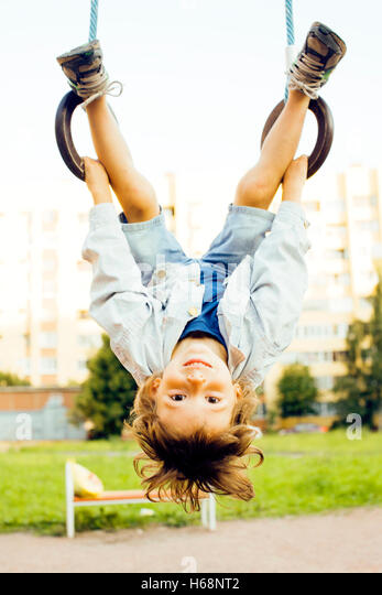 little cute boy hanging on gymnastic ring - Stock Image