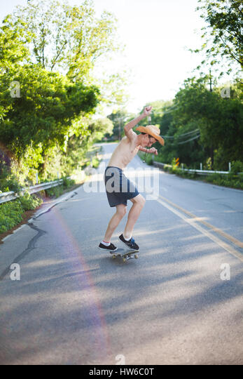 Boy skateboarding down the road - Stock Image