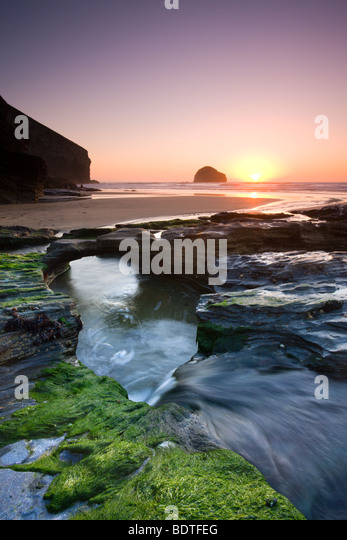 Water channel flowing beneath natural rock arch at Trebarwith Strand beach in Cornwall, England. Spring (April) - Stock-Bilder