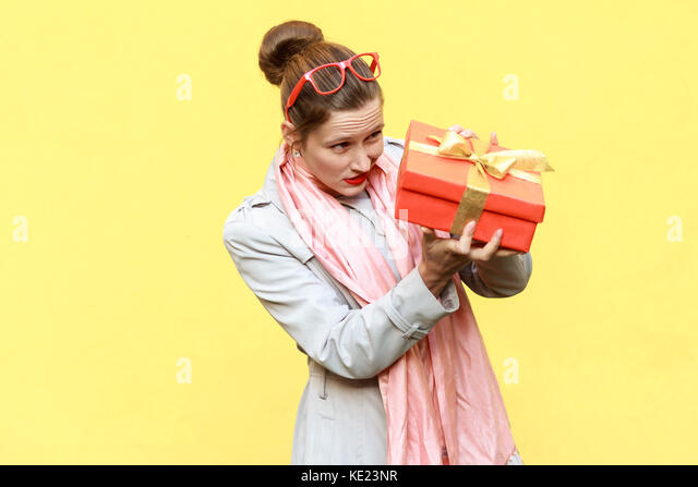 Hmm what is it! Cunning woman looking at gift box and want too open. Yellow background. Studio shot - Stock Image