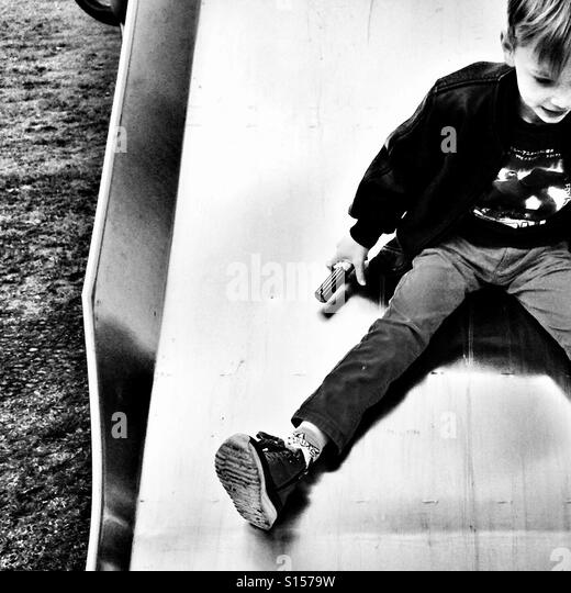 Boy on a slide - Stock-Bilder