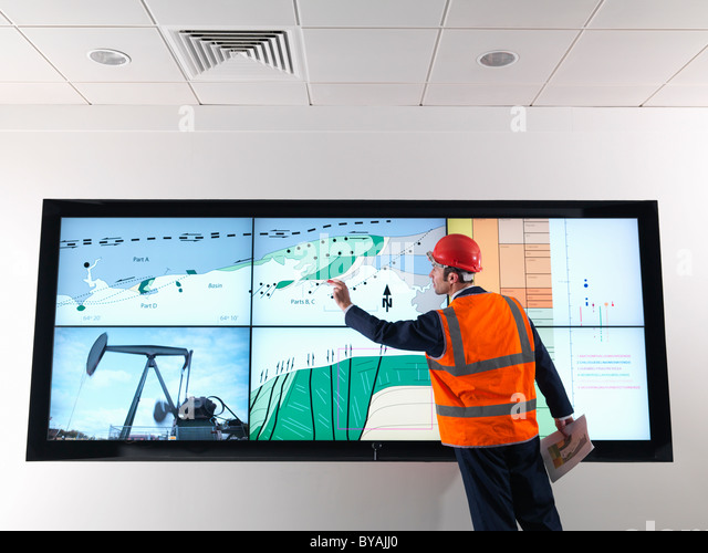 Oil worker with geology screen - Stock Image