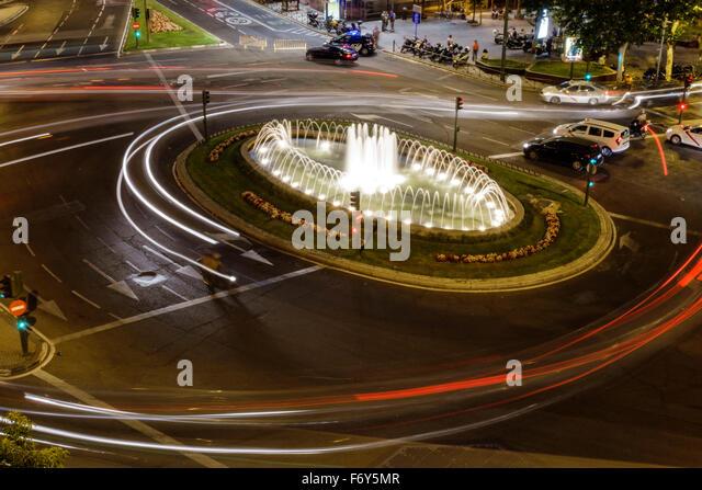 Spain Europe Spanish Hispanic Madrid Chamberi Plaza Alonzo Martinez dusk night nightlife traffic circle lit - Stock Image