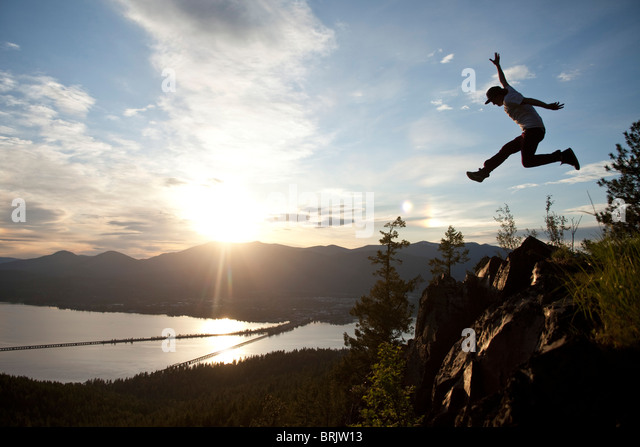 Young man soaring at sunset next to a large cliff overlooking  a lake. - Stock Image