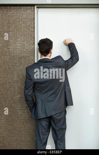 Businessman knocking on door, rear view - Stock Image