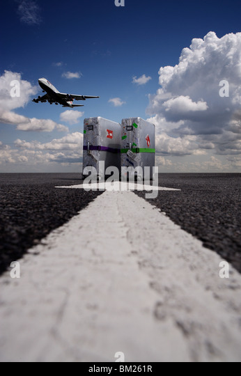 Suitcases with aircraft taking off - Stock Image