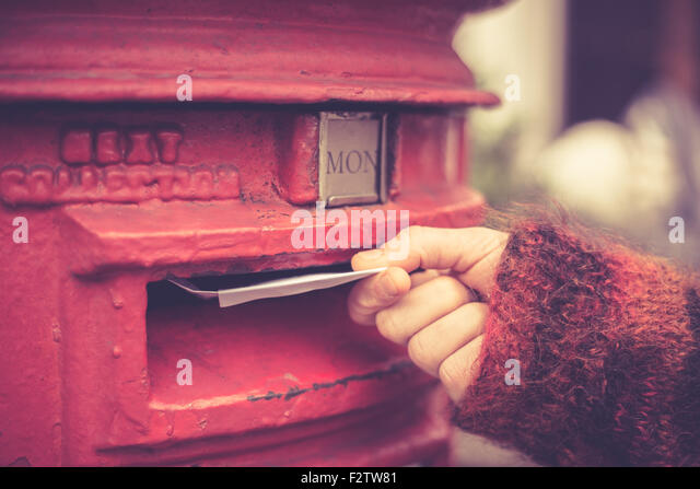 Closeup on a woman's hand as she is posting a letter - Stock Image