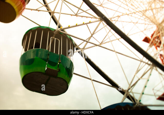 A green car on a ferris wheel in sunny weather - Stock Image