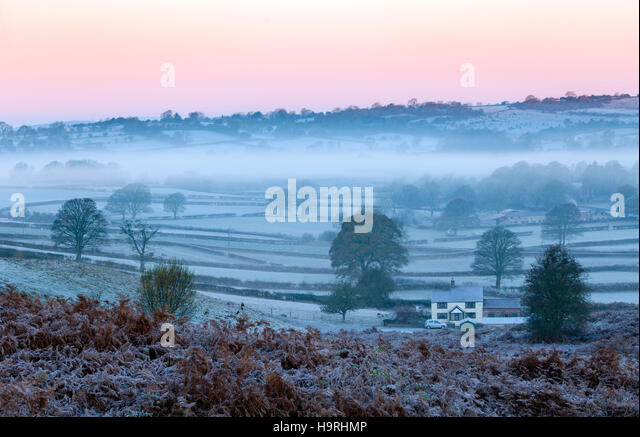 A farm house in the village of Rhes-y-Cae surrounded by morning frost and atmospheric mist - Stock Image