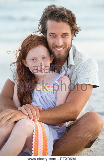 Portrait of father and daughter, smiling at camera, embracing on sunny beach - Stock Image