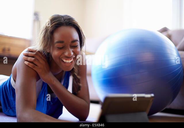 Young woman on a training break, using digital tablet in sitting room - Stock-Bilder