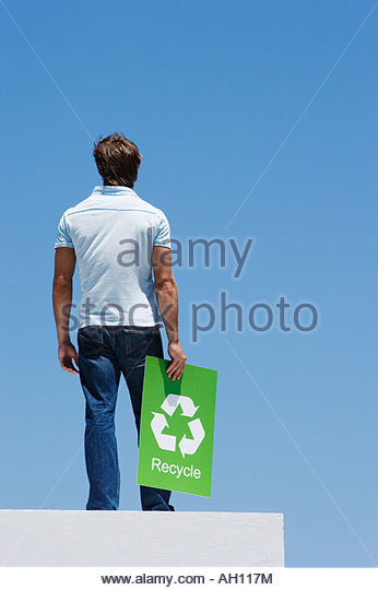 A man holding a recycling sign atop a wall - Stock Image