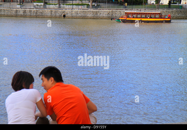 Singapore Singapore River Boat Quay Asian man woman couple romantic water taxi cruise boat - Stock Image