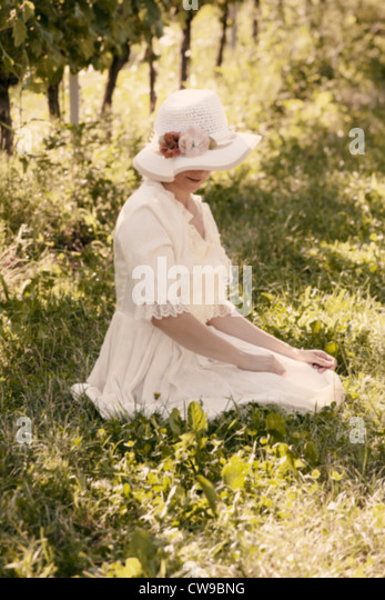 a woman in a white Victorian dress sitting on the grass between vines - Stock-Bilder