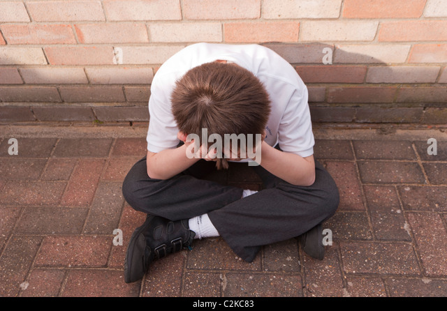 A MODEL RELEASED picture of an eleven year old boy looking depressed outdoors wearing his school uniform in the - Stock Image