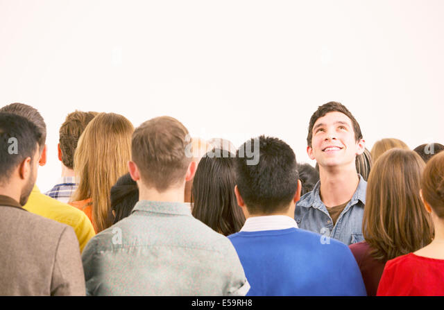 Man standing out from the crowd - Stock Image