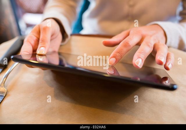 Female digital tablet mail message computer bar restaurant - Stock Image