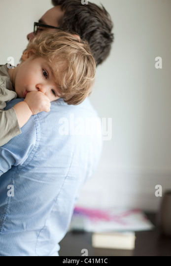 Toddler boy resting head on father's shoudler - Stock-Bilder