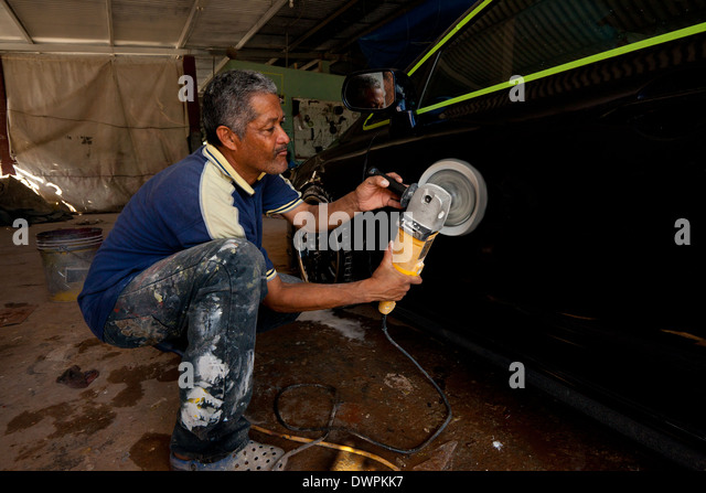 The owner the car workshop, Santos, is polishing a car for a client in Penonome, Cocle province, Republic of Panama. - Stock-Bilder