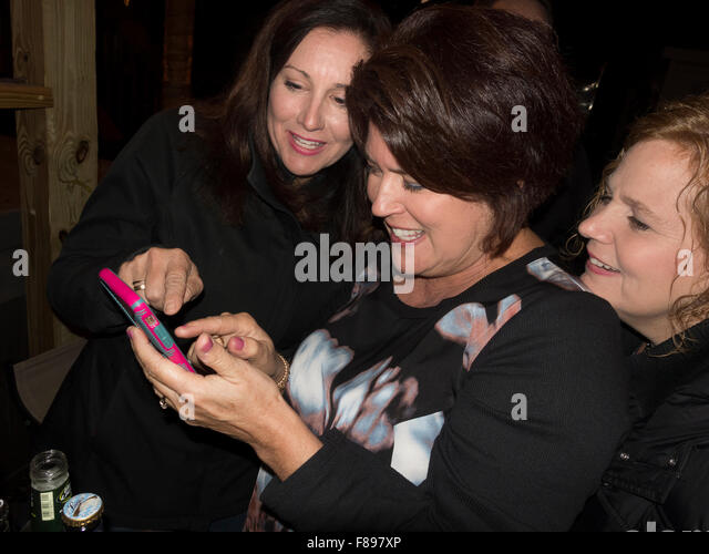 Women at party deciding on what selfie goes on line. Downers Grove Illinois IL USA - Stock Image