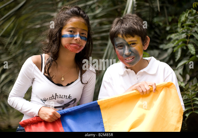 Colombian children wearing face paint hold a Colombian flag at an anti-FARC march - Stock Image