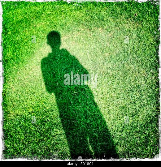 Shadow of person on grass. Selfie, London, UK. Hipstamatic, iPhone. - Stock Image