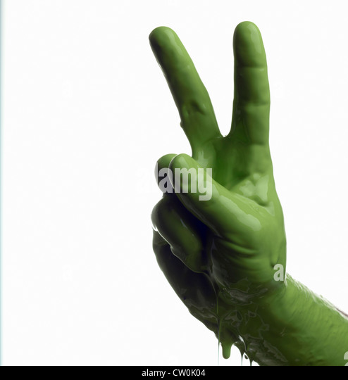 Green painted hand making peace sign - Stock-Bilder