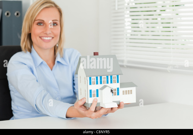 Woman showing model house - Stock Image