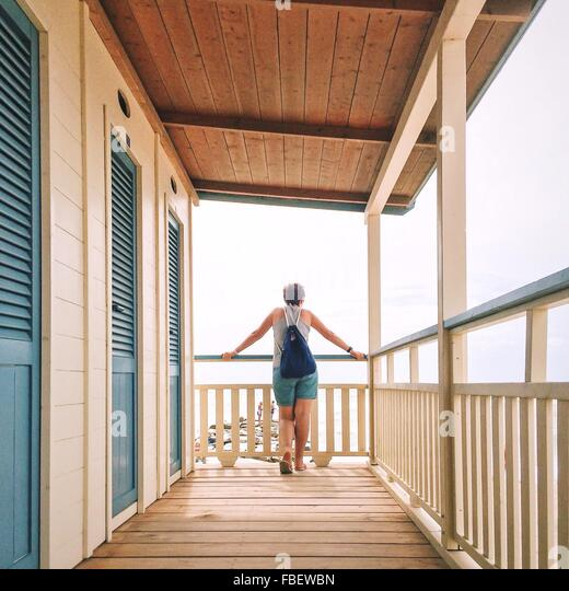 Rear View Of Woman Standing By Railing At Seaside - Stock Image