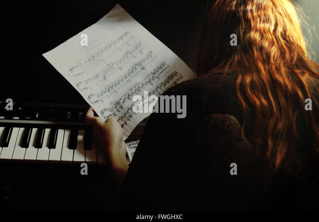 Woman By Piano Holding Musical Notes - Stock Image