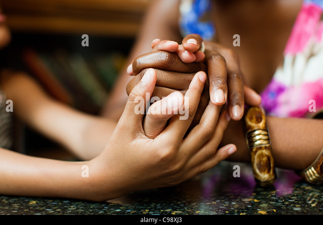 Mother and daughter holding hands in cafe - Stock-Bilder