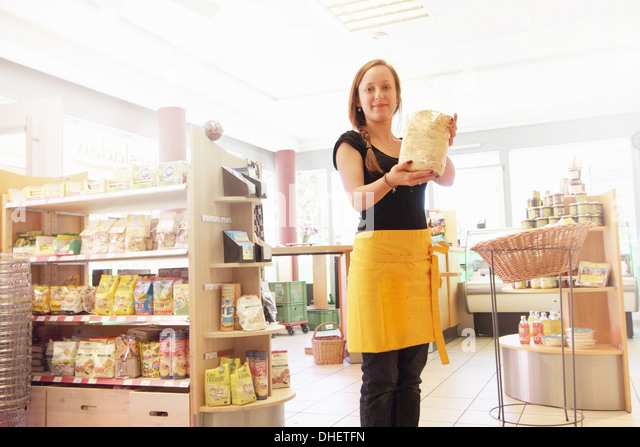 Woman working in organic food market, holding packet of food - Stock Image
